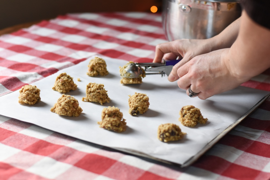 Hands are scooping cookie dough onto cookie sheet. Several scoops are already on the tray.