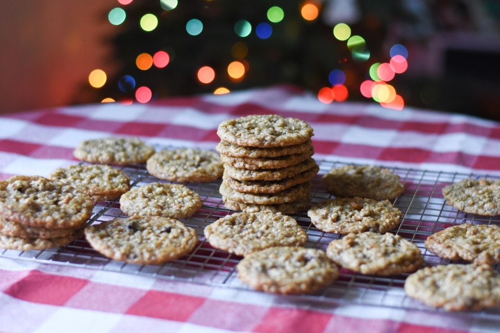 Oatmeal cookies in front of a lit up Christmas tree with multi-colored lights. The cookies are on a cooling rack over a red and white checked tablecloth.