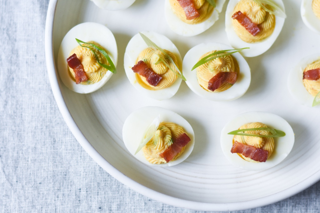 Bacon deviled eggs with bacon garnish and scallions, keto