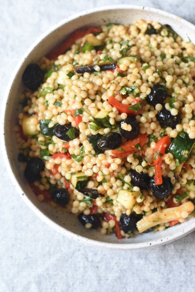 close up of pear couscous with grilled vegetables and olives